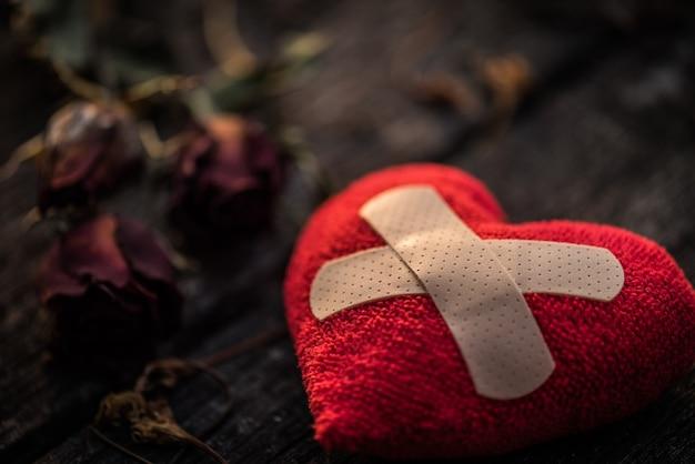 Rotes herz mit getrockneter rotrose auf hölzernem hintergrund. herz gebrochenes konzept.