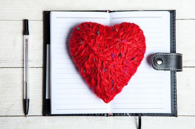 Rotes herz mit notizbuch und stift