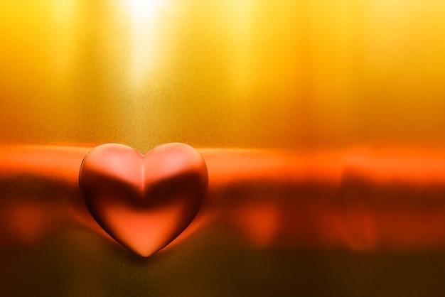 Rotes herz mit reflexen auf einem glänzenden goldenen hintergrund. festlicher hintergrund für valentinstag mit kopienraum. Premium Fotos