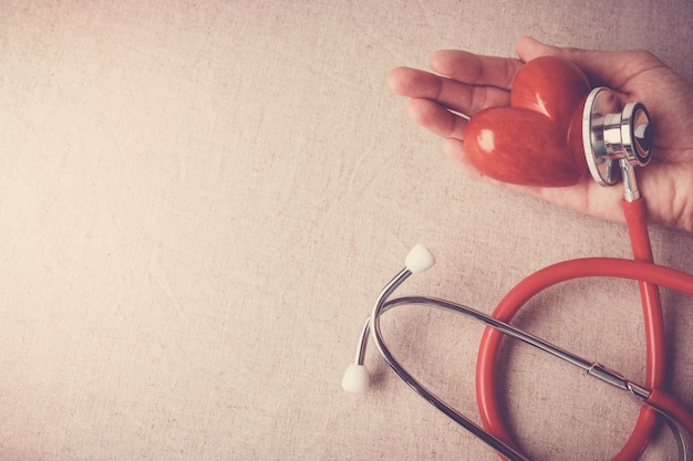 Rotes herz mit stethoskop, herzkrankenversicherungskonzept