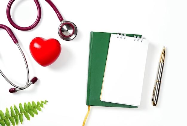 Rotes herz mit stethoskop und notebook auf weißem hintergrundgesundheits- und medizinkonzept