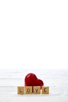 Rotes herz mit valentinstag-textliebe holzbriefblöcke auf weißem tisch