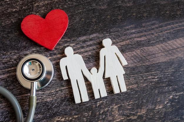 Rotes herz, stethoskop und ikonenfamilie auf hölzernem schreibtisch. krankenversicherungskonzept