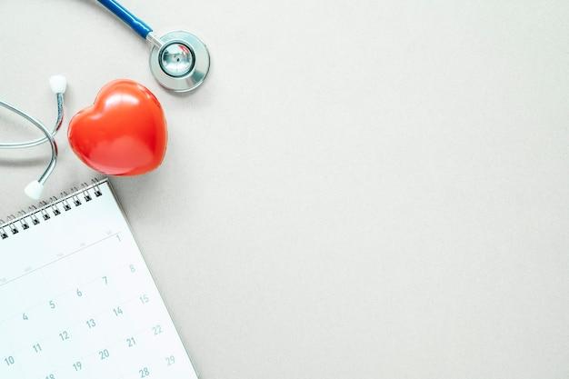 Rotes herz, stethoskop und kalender auf weißer tabelle mit freiem raum.