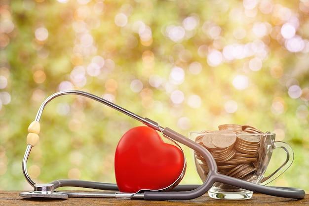 Rotes herz, stethoskope und geld prägen im glas auf hölzernem hintergrund selektiver fokus.