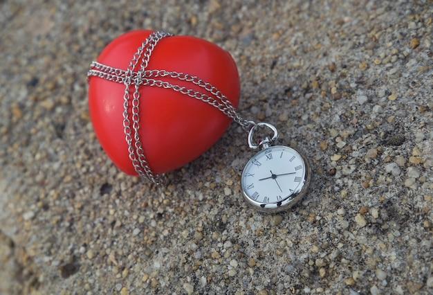 Rotes herz und alte weinlesetaschenuhr auf rauem zementhintergrund