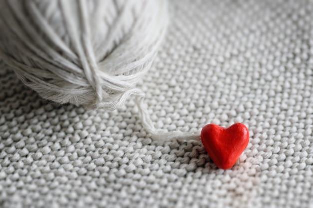 Rotes herz und ein ball von threads auf einem gestrickten hintergrund