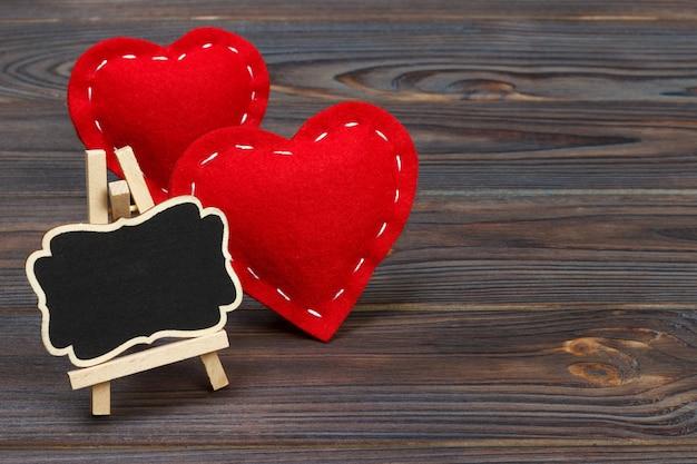 Rotes herz und kleine tafel mit kopienraum auf einem schwarzen
