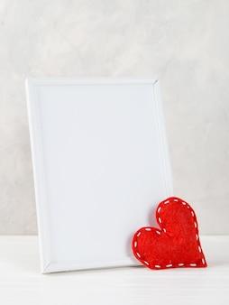 Rotes herz und rahmen gegen die weiße wand, konzept, eine postkarte für valentinstag.