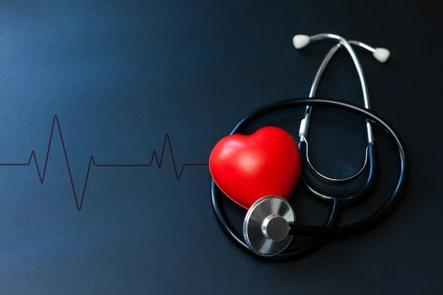 Rotes herz und stethoskop auf blauem papier. flache verlegung wesentlicher gegenstände für den arzt, der den patienten im krankenhaus behandelt und pflegt.