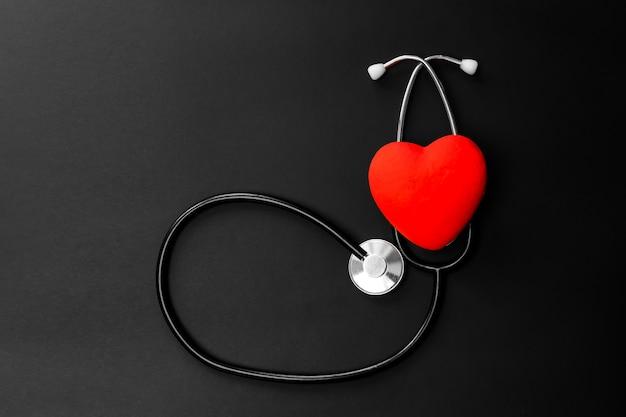 Rotes herz und stethoskop auf schwarzem papier. flache verlegung wesentlicher gegenstände für den arzt, der den patienten im krankenhaus behandelt und pflegt.