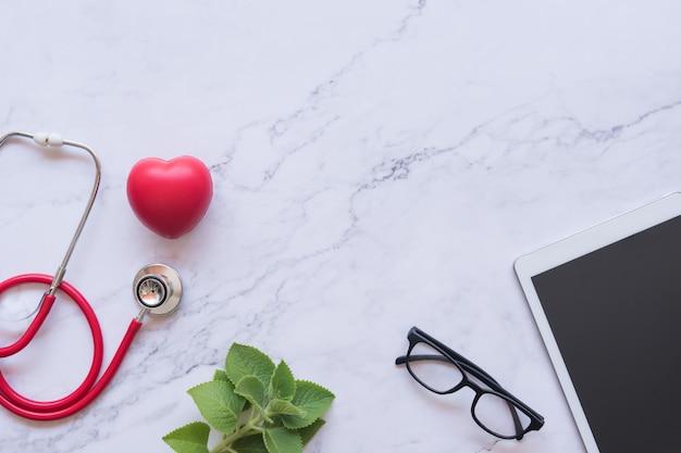 Rotes herz und stethoskop und tablette auf weißem marmorhintergrund