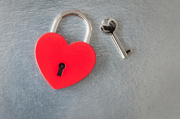 Rotes herz vorhängeschloss und schlüssel auf silber für valentinstag