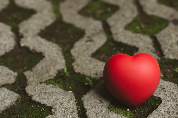 Rotes herz wird auf betonboden gelegt