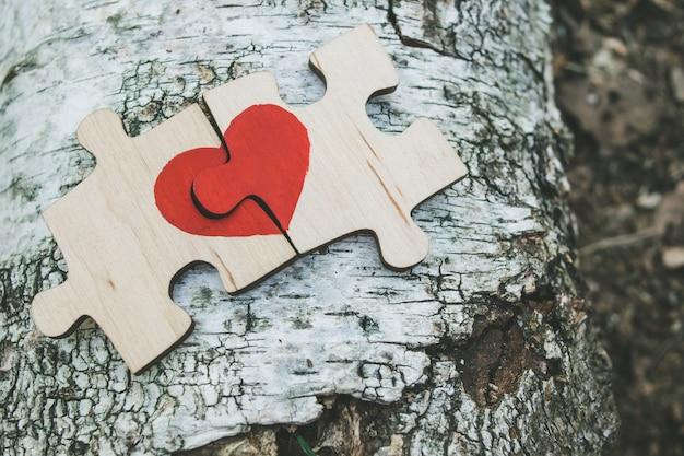 Rotes herz wird auf die stücke des hölzernen puzzlespiels gezeichnet, das nebeneinander auf hölzernem hintergrund liegt. liebe . valentinstag