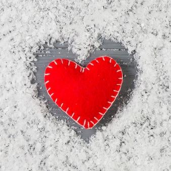 Rotes herz zwischen dekorativem schnee auf hölzernem schreibtisch