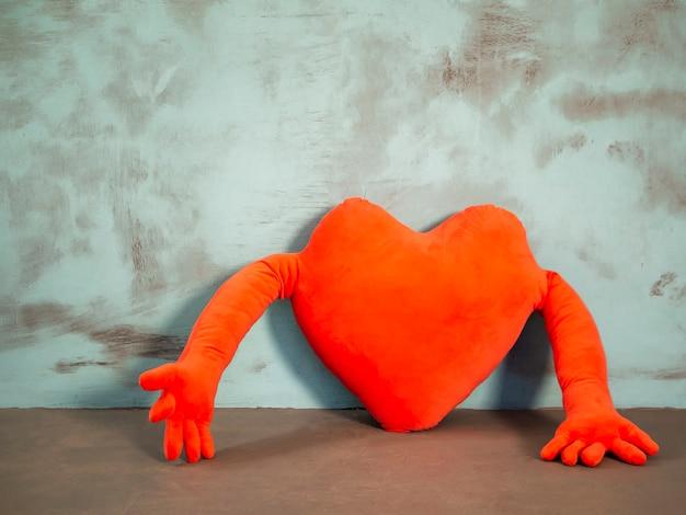 Rotes herzförmiges kissen der valentinsgrüße mit den händen auf blau