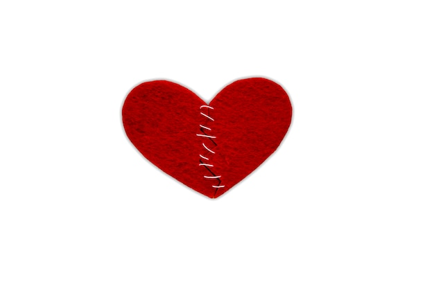 Rotes herzgewebe mit weißen fäden auf weißem hintergrund, getrennt. das konzept der traurigkeit, der unglücklichen liebe, des gebrochenen herzens.