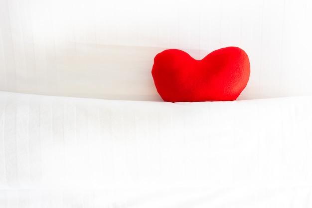 Rotes herzkissen bedeckt durch weiße decke auf dem bett für liebe