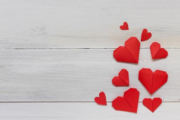 Rotes herzorigamipapier auf weißem hölzernem hintergrund, romance und valentinstagkonzept