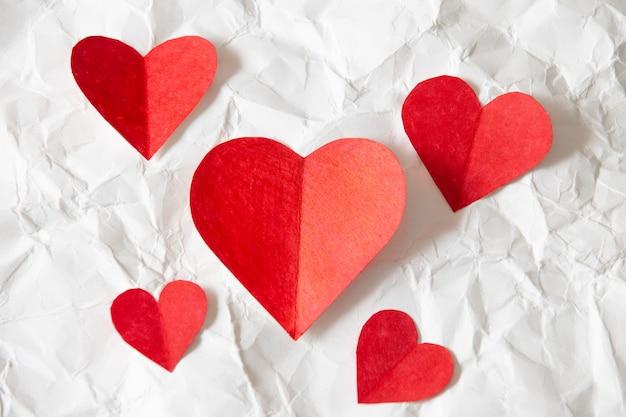 Rotes herzpapier auf weißem zerknittertem papier, schöner hintergrund des valentinstags