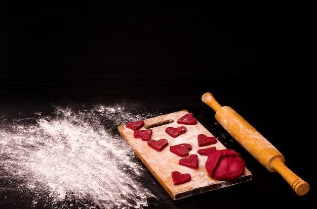 Rotes herzplätzchen und ein stück teig auf dem hölzernen brett, backend für valentinstag