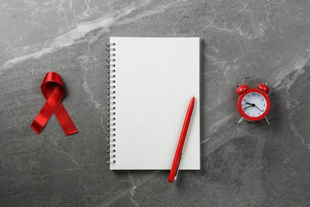 Rotes hilfsband auf leerem notizbuch mit rotem wecker auf grauer marmortisch-draufsicht, symbol des kampfes gegen hiv und hilfsmittel, flache lage