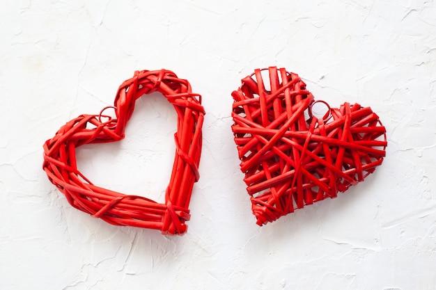 Rotes hölzernes herz im weinlesestil lokalisiert auf weißem strukturiertem betonhintergrund. rustikale wohnkultur zum valentinstag. herzform. valentinstagskartenkonzept. medizin, gesundheit, krankheit. liebeskonzept