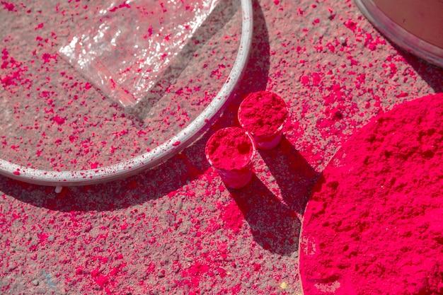Rotes holi-farbpulver in gläsern und teller