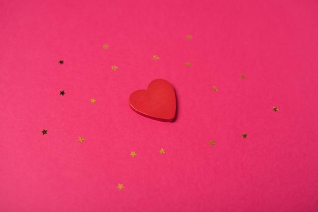 Rotes holzherz und kleine goldene sterne. valentinstag konzept. flache lage, draufsicht.