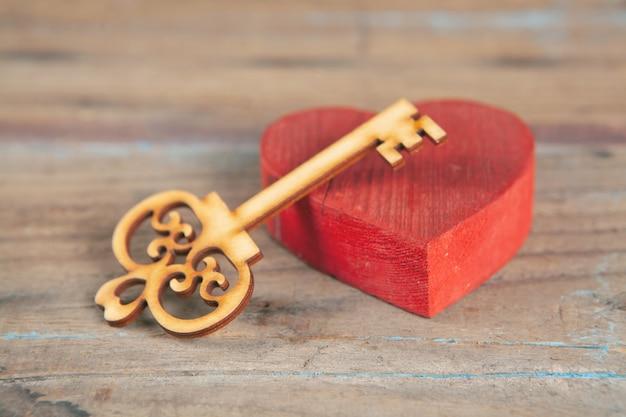Rotes holzherz und schlüssel auf dem tisch