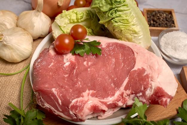 Rotes kalbfleischhieb auf einer platte auf einem hölzernen brett