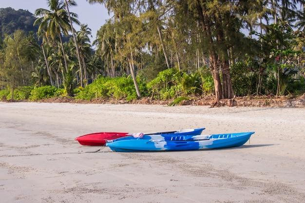 Rotes kayak fahrendes boot auf dem tropischen strandbereich ao prao in koh kood insel, trat-provinz, thailand.
