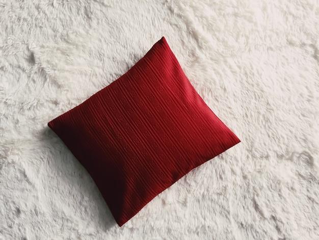 Rotes kissen-wurfskissen auf weißer flauschiger karierter decke als flache lage