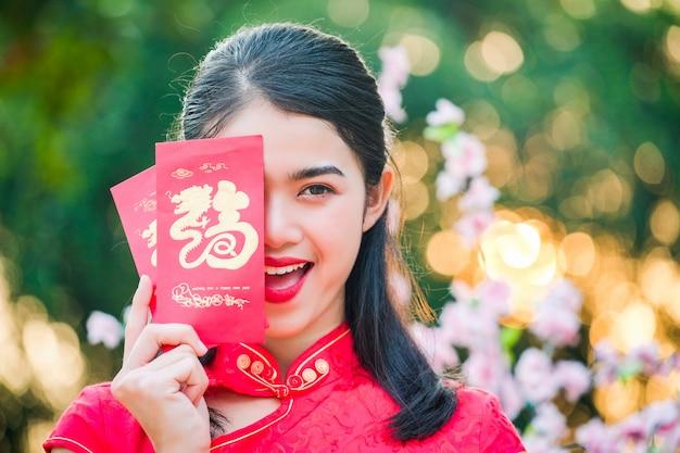 Rotes kleid der chinesischen frau des porträts traditionelles cheongsam im chinesischen tempel.
