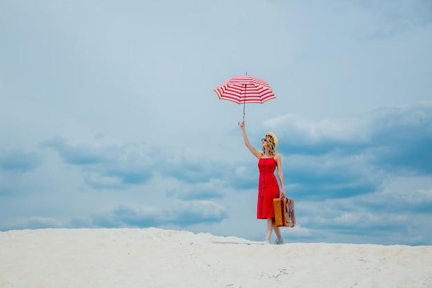Rotes kleid mit sonnenschirm und koffer am strand