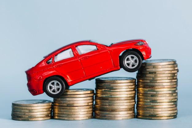 Rotes kleines auto, das über den steigenden münzenstapel gegen blauen hintergrund reitet