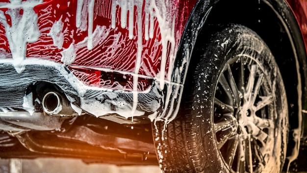 Rotes kompaktes suv-auto mit sport und modernem design waschend mit seife. auto bedeckt mit weiß