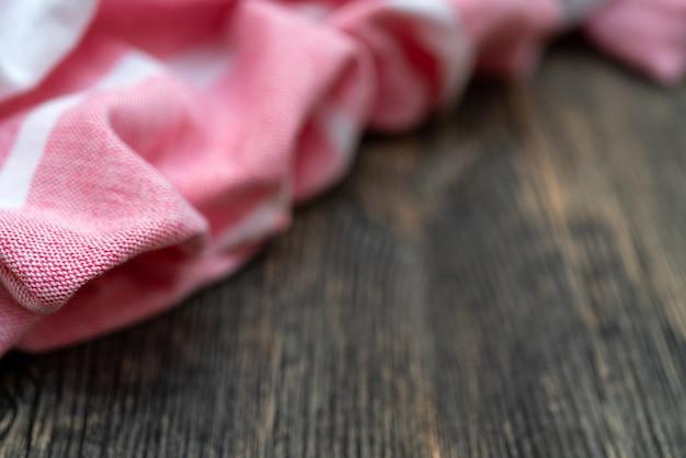 Rotes küchentuch liegt auf holztisch. textur aus lackiertem holz. strukturierte stofffalten.