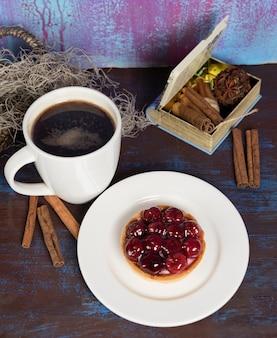 Rotes leckeres kuchenstück mit schwarzem kaffee