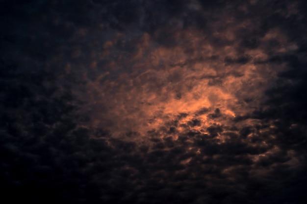 Rotes licht der sonne im dunklen bewölkten sonnenunterganghimmel. dramatischer himmel mit schönem muster der flauschigen wolken. mentale kraft oder psychische kraft. kraft der natur. exotische wolkenlandschaft. konzept des klimawandels.