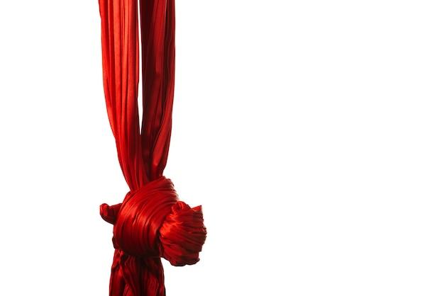 Rotes luftband in knoten gebunden für luftakrobatik und gymnastik, die auf weißem hintergrund hängt. berufskonzept für kinder und erwachsene mit der entwicklung von beweglichkeit und gleichgewichtsapparat
