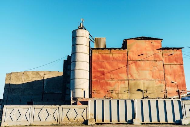 Rotes metallisches industriegebäude hinter weißem zaun