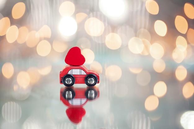 Rotes miniaturauto, das ein rotes herz trägt