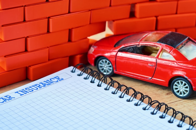 Rotes miniaturauto stieß in einer backsteinmauer- und autoversicherungsform zusammen