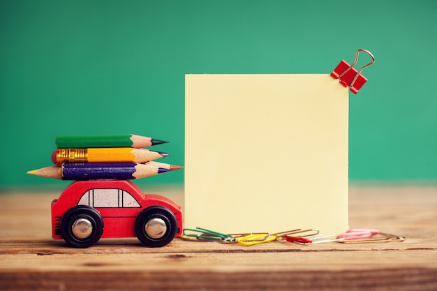 Rotes miniaturauto, tragen bunte bleistifte auf holztisch. zurück zum schulkonzept