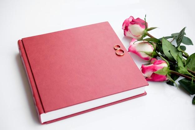 Rotes mit leder überzogenes hochzeitsbuch oder album mit zwei eheringen und drei rosen liegt auf weiß