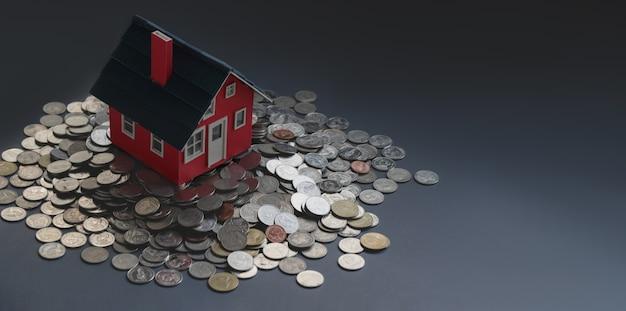 Rotes modell des kleinen hauses auf stapel münzen