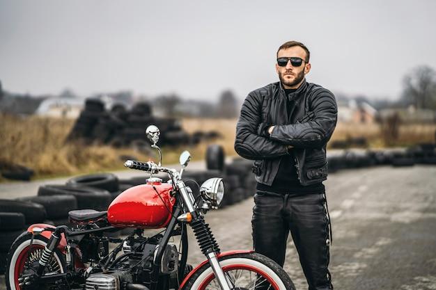 Rotes motorrad mit mitfahrer. ein mann in schwarzer lederjacke und hose steht mit verschränkten händen auf der straße neben einem motorrad. reifen werden auf den hintergrund gelegt