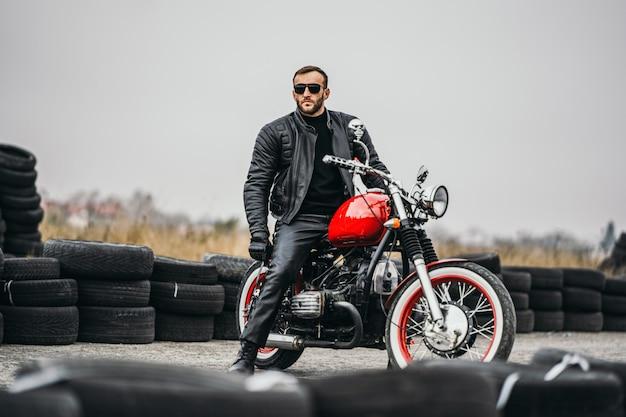 Rotes motorrad mit mitfahrer. ein mann in schwarzer lederjacke und hose steht seitlich mitten auf der straße. reifen werden auf den hintergrund gelegt
